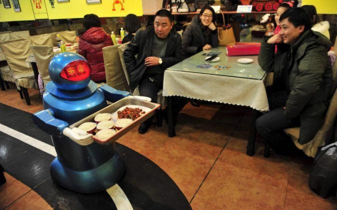 Un robot hace las labores de camarero en un restaurante de Harbin...