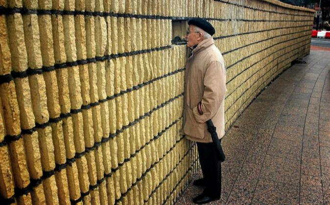 Un jubilado mira por el hueco de un muro.