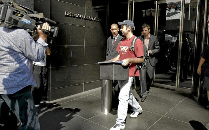 Un empleado sale con una caja con sus pertenencias de la sede central...