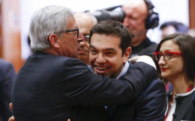 El primer ministro griego, Alexis Tsipras (dcha.), saluda al...