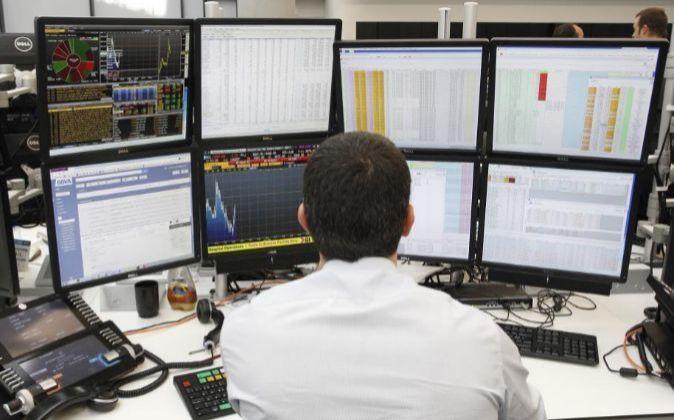 Imagen de un trader frente a las pantallas con la información de los...