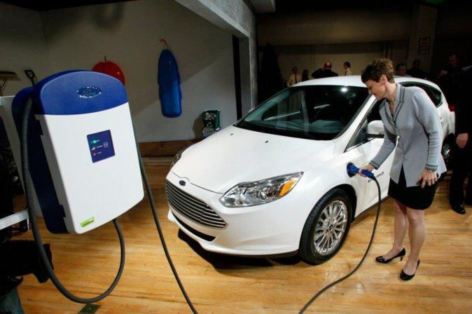 Imagen de un Ford Focus eléctrico junta a una estación de recarga...