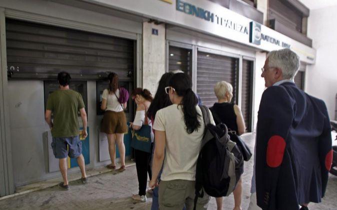 Los griegos hacen cola frente a los cajeros automáticos para retirar...