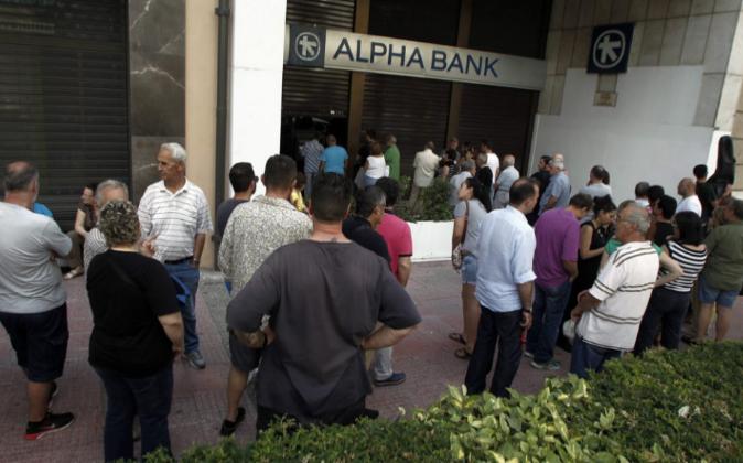 Ciudadanos griegos hacen cola a las puertas de una entidad bancaria.