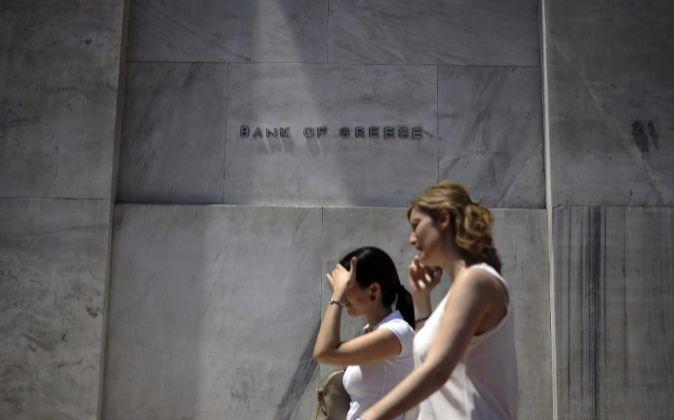 Dos mujeres delante de la sede del Banco central heleno.