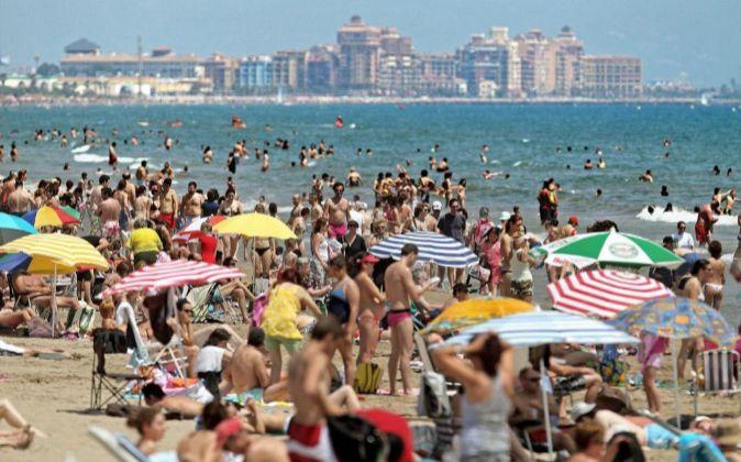 Cientos de personas disfrutan en una playa de Valencia.