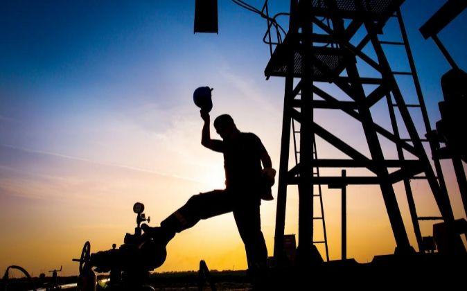Silueta de un trabajador en una refinería petrolífera.