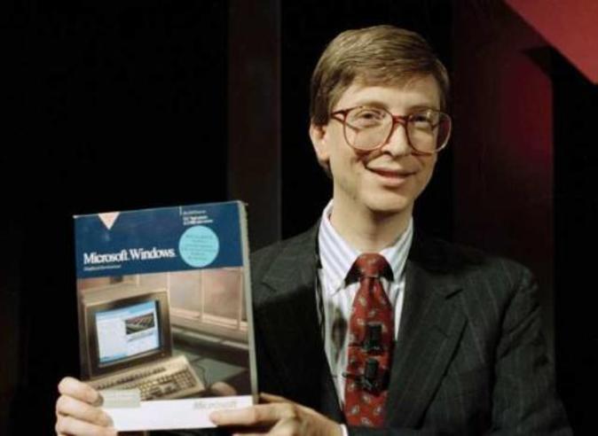 Un joven Bill Gates posa con el manual de usuario de Windows.