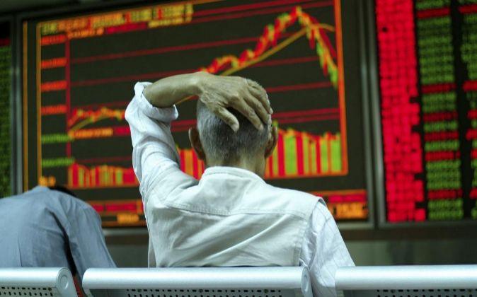 Un inversor revisa una pantalla de la Bolsa de Pekín.