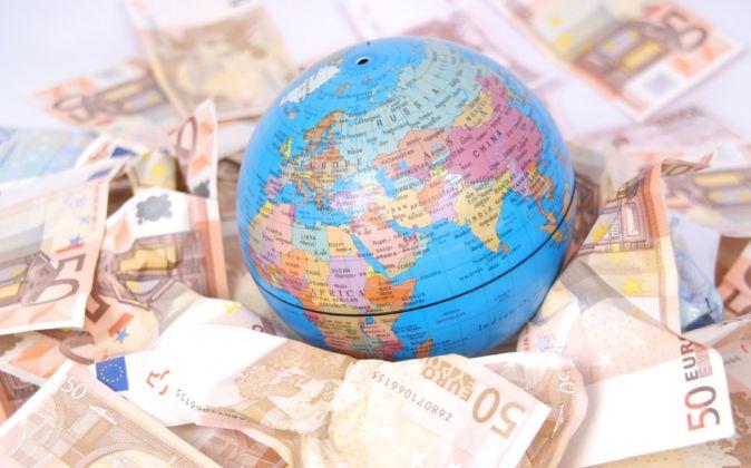 Bola del mundo rodeada de billetes de 50 euros.
