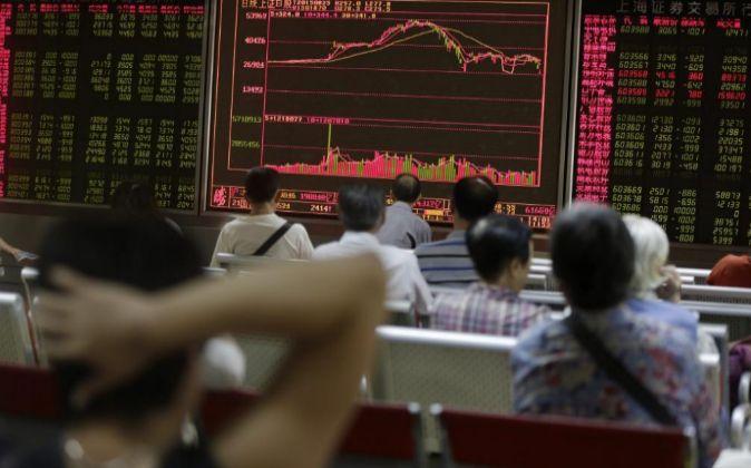 Inversores chinos sentados ante unas pantallas con la evolución...
