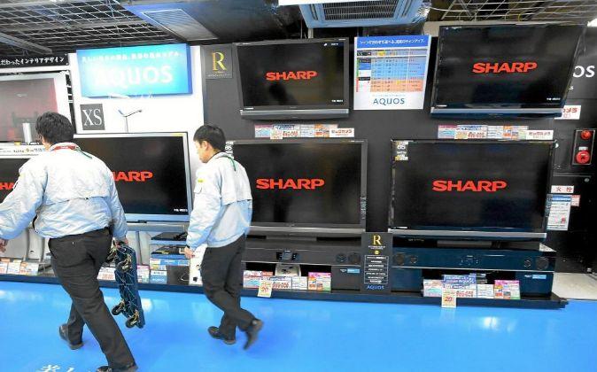 Dos hombres pasan por delante de unas pantallas Sharp