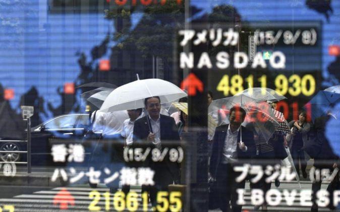 Peatones junto a las pantallas que la Bolsa de Tokio tiene instaladas...