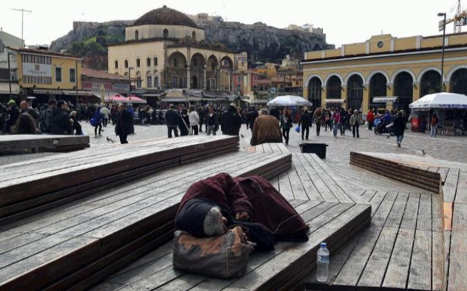 Una anciana indigente duerme en un parque en Atenas.
