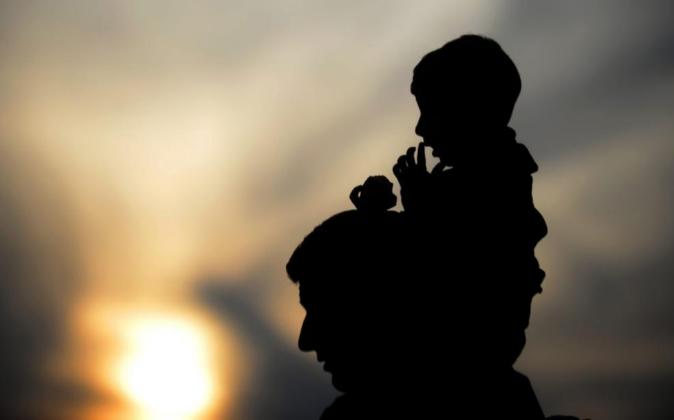 Un hombre carga a un niño mientras camina por Macedonia.