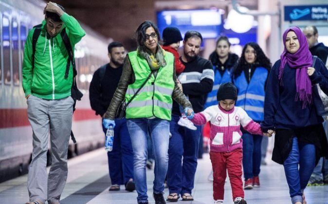 Una familia de refugiados camina por la estación de Colonia.