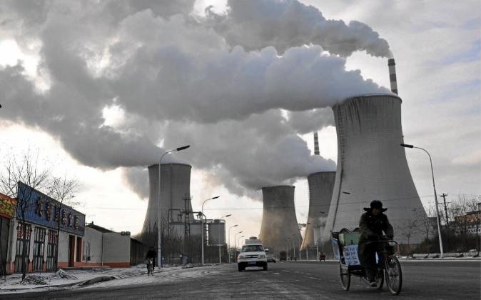 Un hombre pasa en bici por delante de una planta térmica en Fuxin...