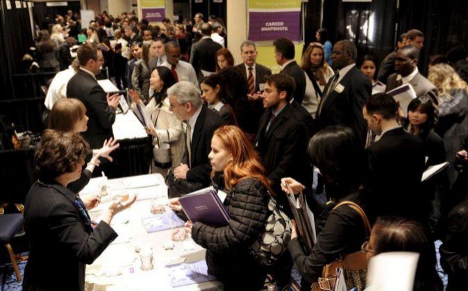 Un grupo de desempleados hace fila para hablar con personal de...