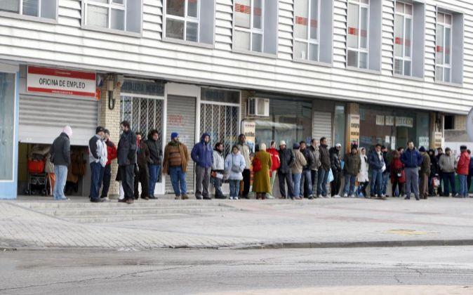 Varias personas forman una larga cola ante una oficina de empleo.
