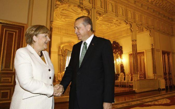 TLa canciller alemana, Angela Merkel, estrecha la mano del presidente...