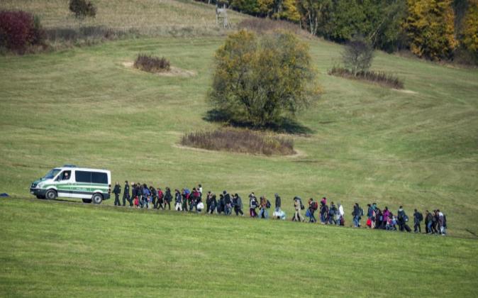 La policía escolta a un grupo de refugiados a un centro de acogida...