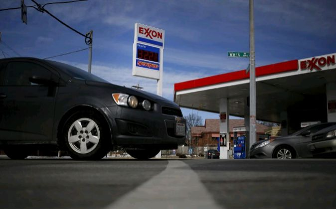 Gas prices are displayed as cars drive past an Exxon Mobil Corp....