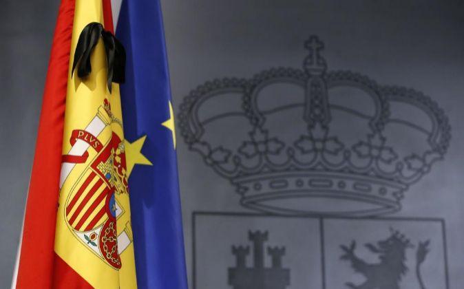 Las banderas española y europea, con un crespón negro, en la sala de...