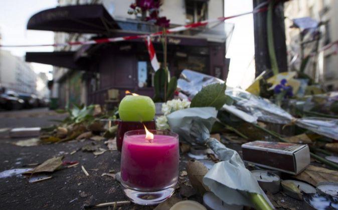 Flores y velas en una calle de París donde ocurrió uno de los...