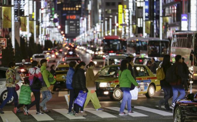 Varios turistas chinos cruzan por la calle principal del distrito de...