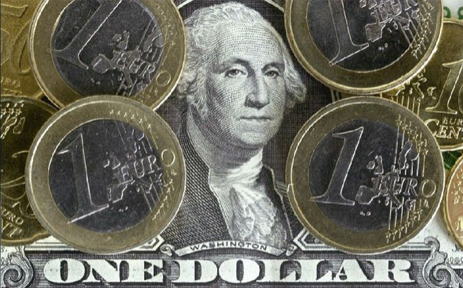 Imagen de monedas de un euro sobre un billete de dólar