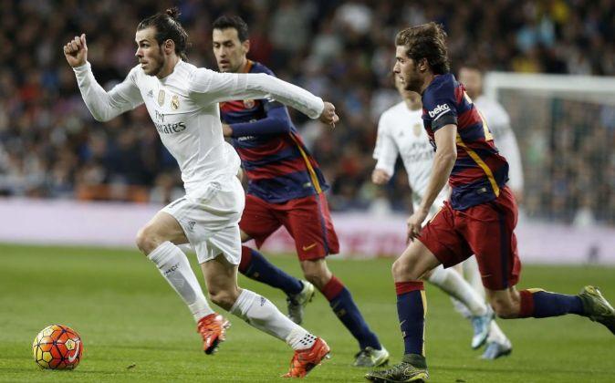 El delantero Galés del Real Madrid Gareth Bale (i) se escapa de...