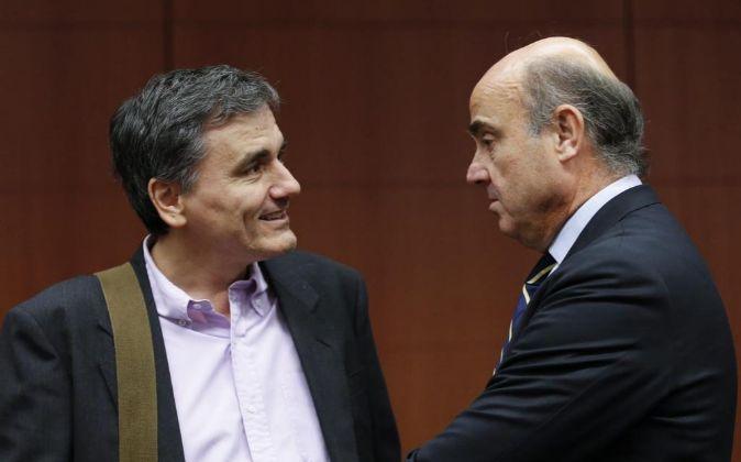 El ministro español de Economía, Luis de Guindos (d) conversa con el...