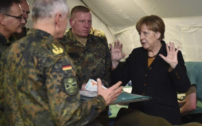 La canciller alemana, Angela Merkel (d) durante una visita al servicio...