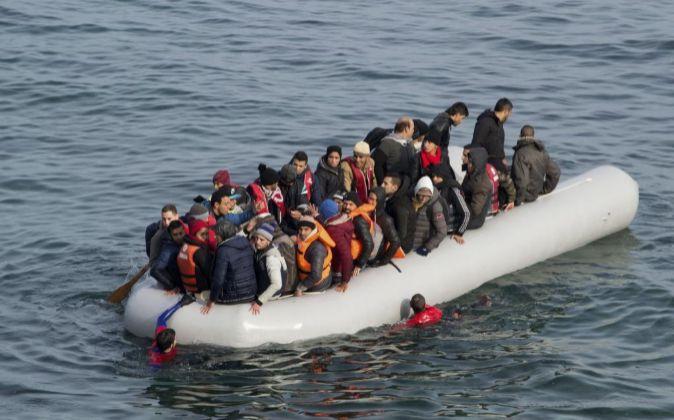 Varios refugiados son conducidos por miembros de la Guardia Costera...