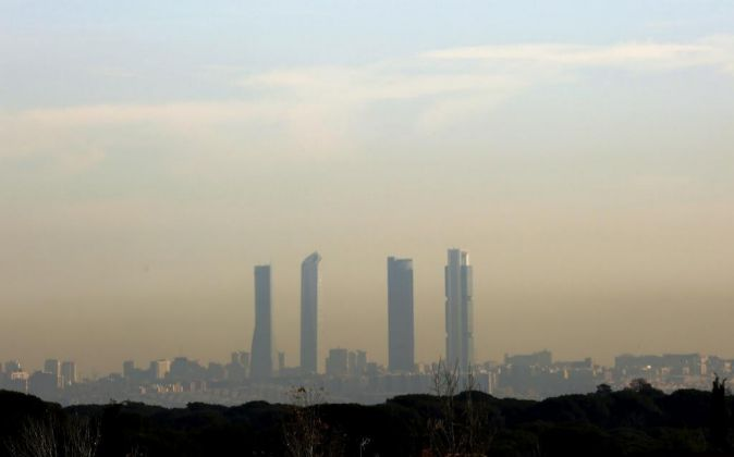 Las Cuatro Torres se perfilan entre la nube de polución de Madrid.