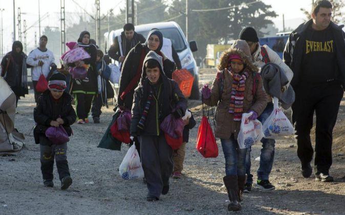 Un grupo de refugiados se dirige a cruzar la frontera entre Grecia y...