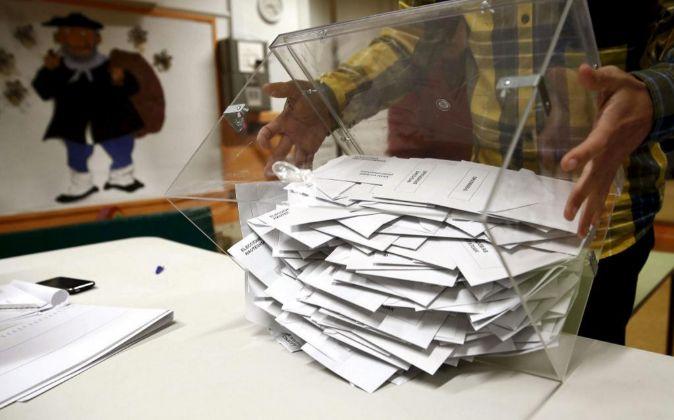 El presidente de una mesa electoral deposita los votos de la urna...