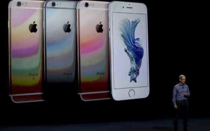 El director ejecutivo de Apple, Tim Cook, habla junto a imágenes del...