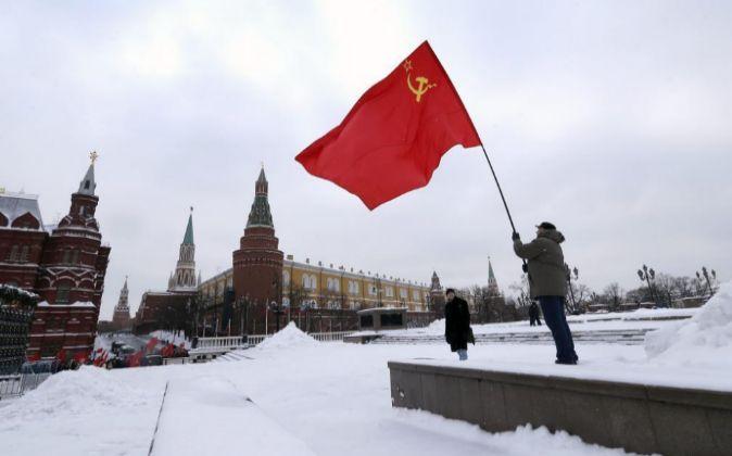Un hombre sostiene una bandera del partido comunista durante la...