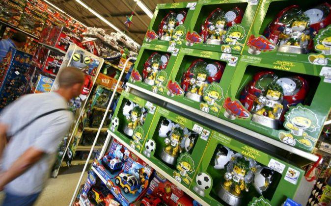 Un cliente pasa junto a una estantería llena de muñecos Zakumi