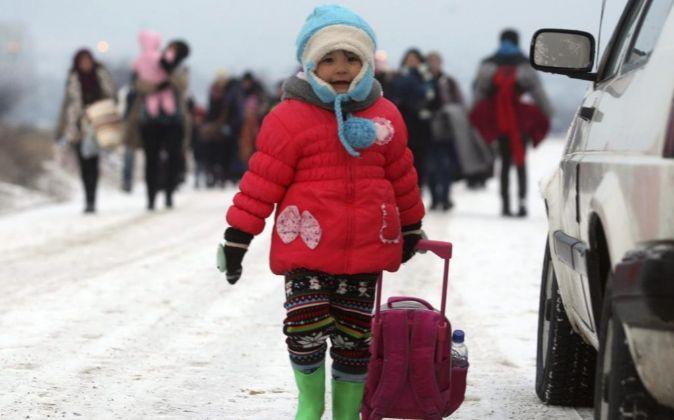 Refugiados sirios, iraquíes y afganos caminan por un camino nevado...