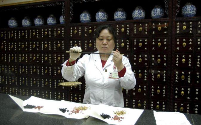 Una mujer prepara medicina tradicional china en Tongrentang, la tienda...