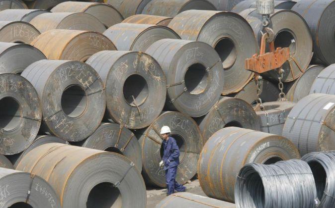 Un trabajador chino camina entre enormes rollos de acero en Shenyang...