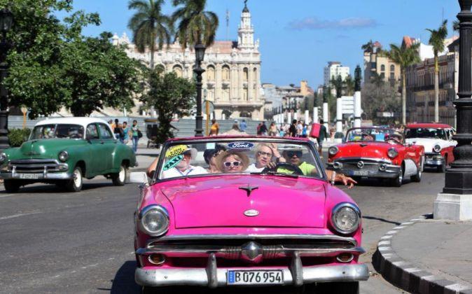 Varios turistas viajan en un vehículo antiguo por una calle de La...