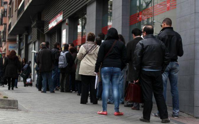 Parados hacen cola junto a una oficina de empleo en Madrid.
