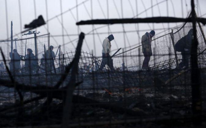 Varios refugiados caminan por un campamento parcialmente destruido en...