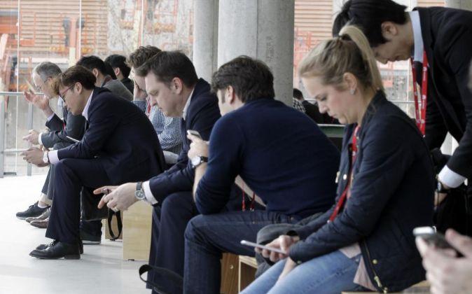 Varios visitantes utilizan sus dispositivos móviles en uno de los...