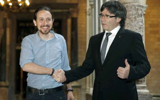El presidente de la Generalitat, Carles Puigdemont (d), saluda al...