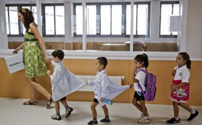 Un grupo de niños en fila se dirigen a clase con la profesora al...