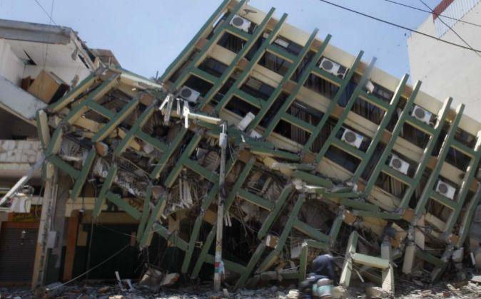 Un hombre pasa junto a varios edificios colapsados ayer en el centro...